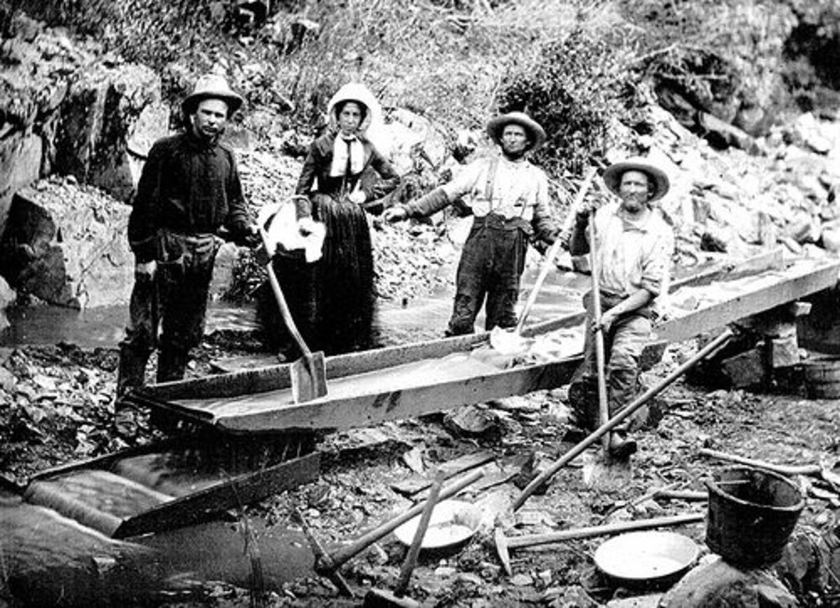 A woman with three men panning for gold during the California Gold Rush in 1850.