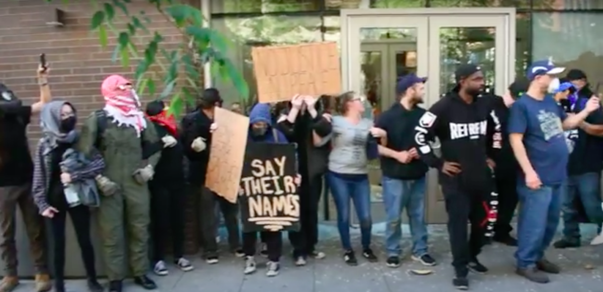 Peaceful Protesters form chain in front of Spokane Nike Store.