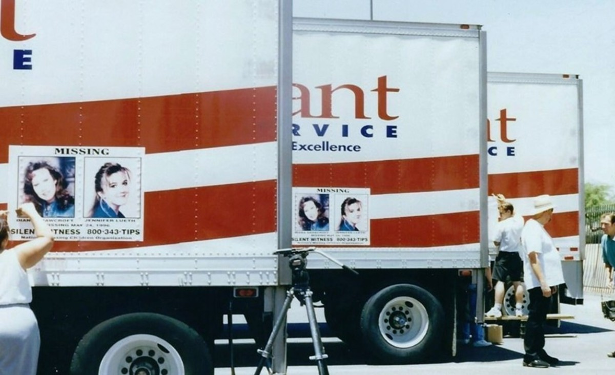 Staff at the National Center for Missing Adults applying full size color posters on local trucks from Alliant Food Service.