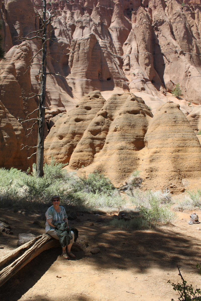Cindy resting in the shade in Red Mountain Amphitheater, Hoodoos in the background.