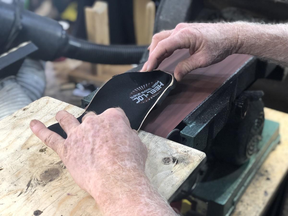 Heel piece being belt-sanded flat