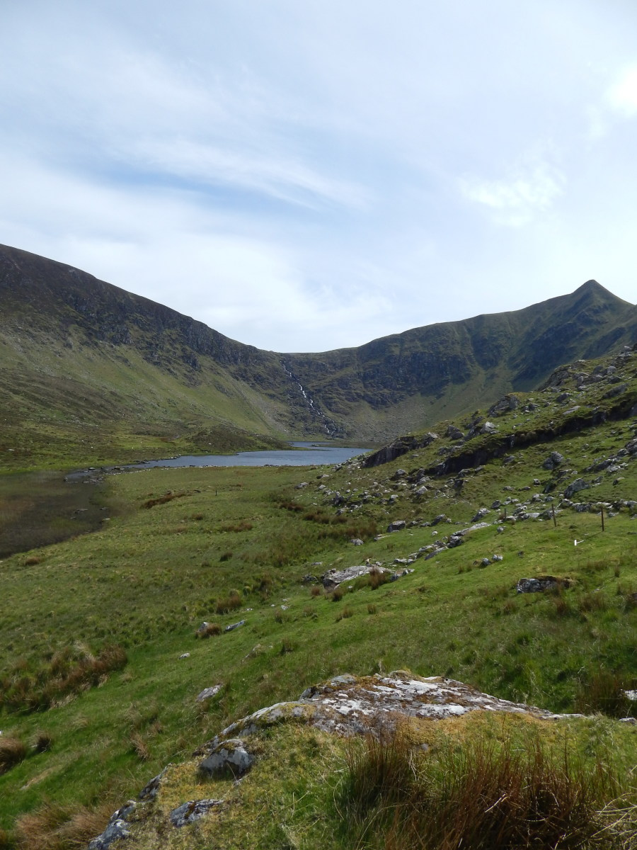 Loch a'Dúin. The ruined fort can be seen on an island in the centre of the lake, with the remains of clocháns (bee hive huts) clustered on the edge of the water.