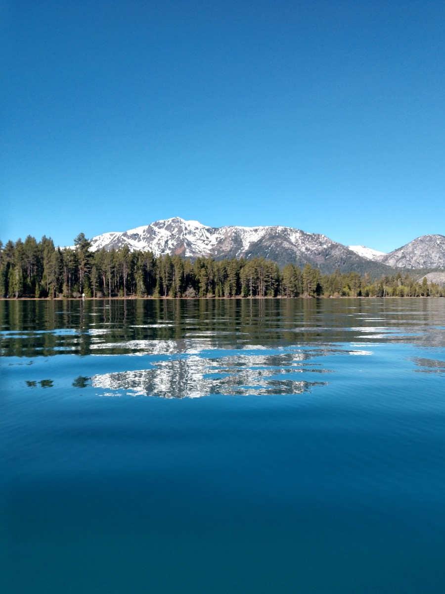 Glassy water set against snowy mountains, just west of Camp Richardson.