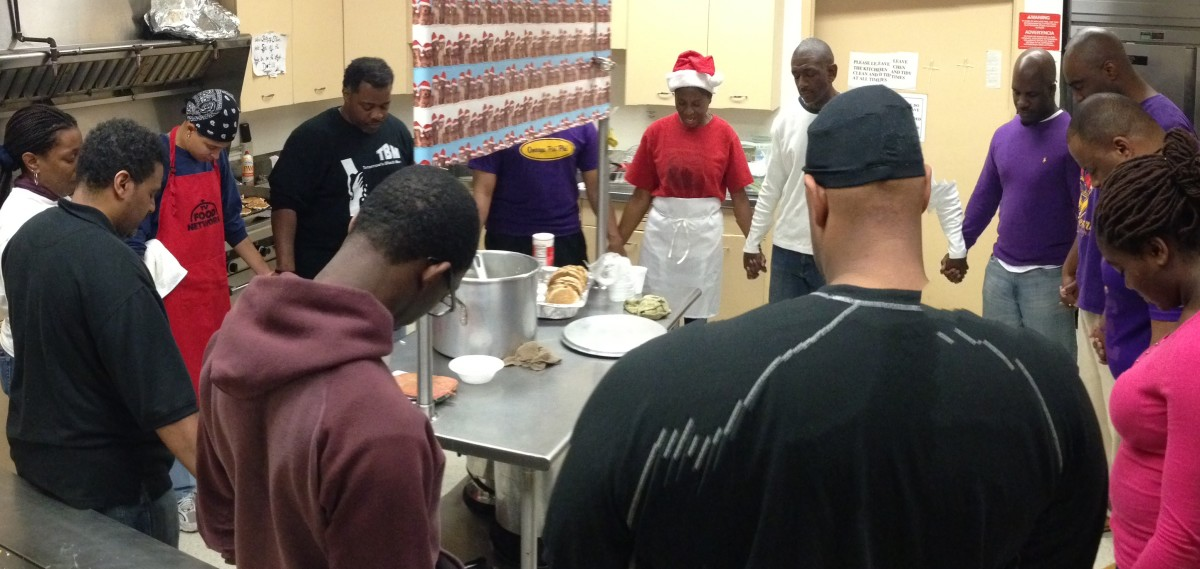 Volunteers pause for prayer in the kitchen before serving breakfast at the Kwanzaa Kitchen.