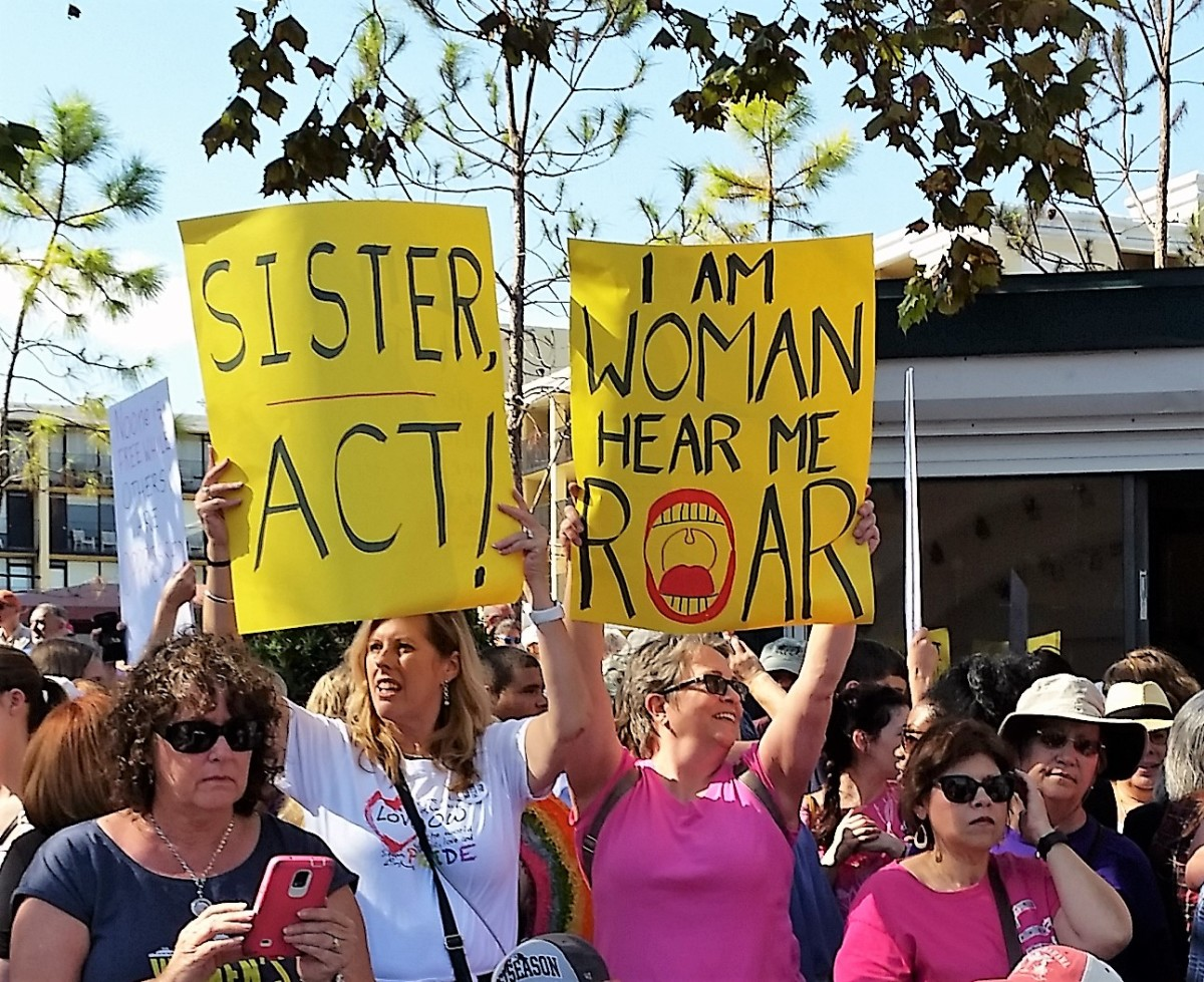 "Sisterhood was a popular theme at the rally and marches. These signs say ""Sister Act"" and ""I Am Woman, Hear Me Roar."" The last one is the title of a song by Helen Reddy."