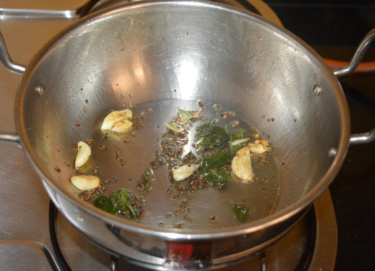 Step two: Heat oil or ghee in a deep-bottomed pan. Add mustard seeds and allow them to crackle. Add cumin seeds, curry leaves, and slightly crushed garlic cloves. Continue to saute until the garlic becomes golden brown.