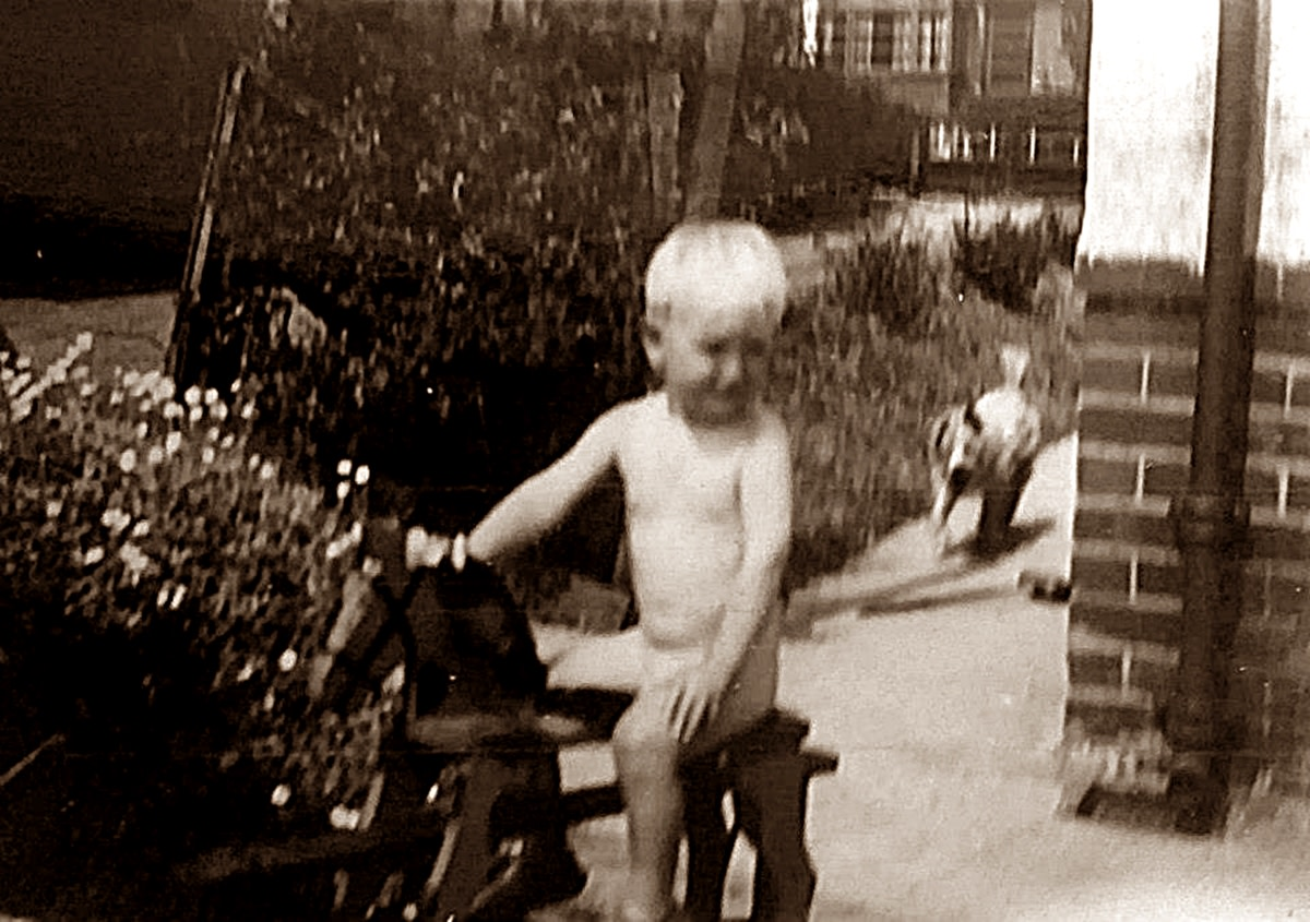 My brother as a toddler playing in the garden. Wherever he went, Peggy, his dog, was never far behind.