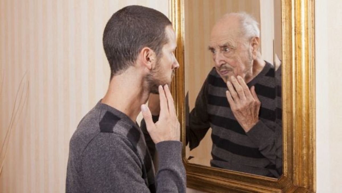 Young man looks in mirror and sees he is old