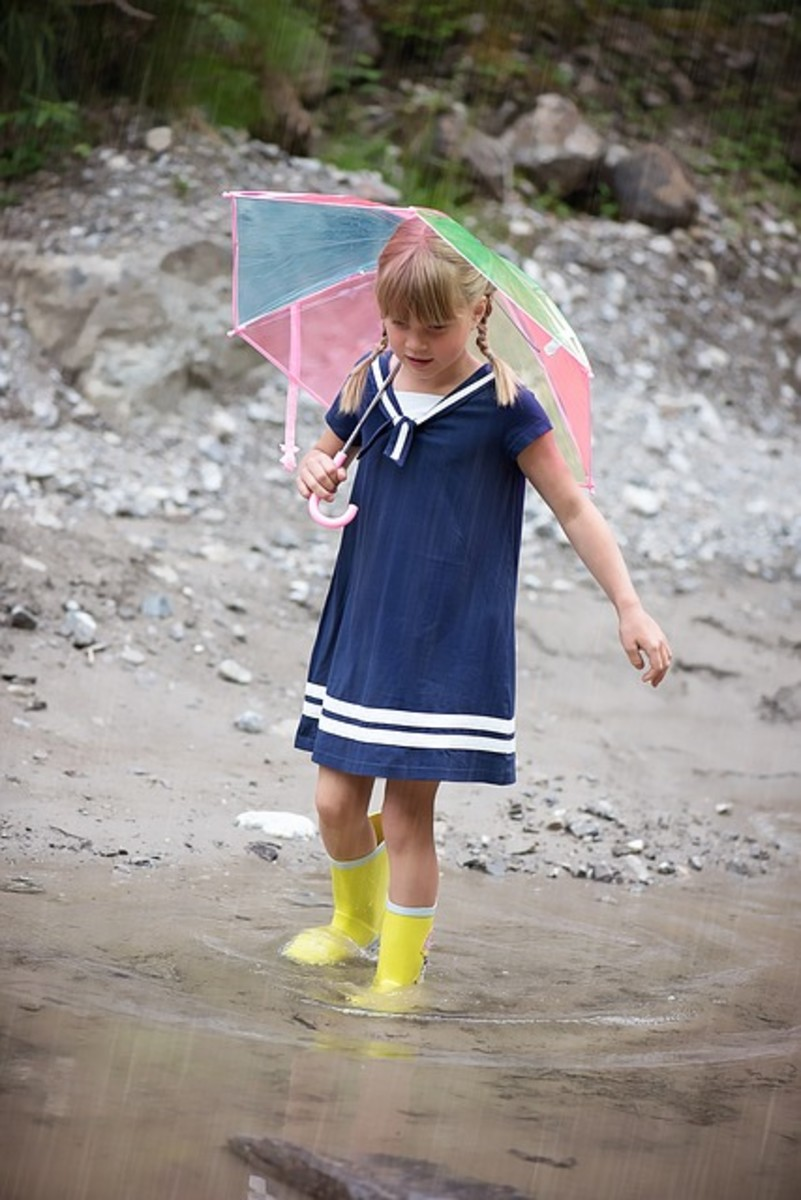 A young girl steps out with umbrella and boots.