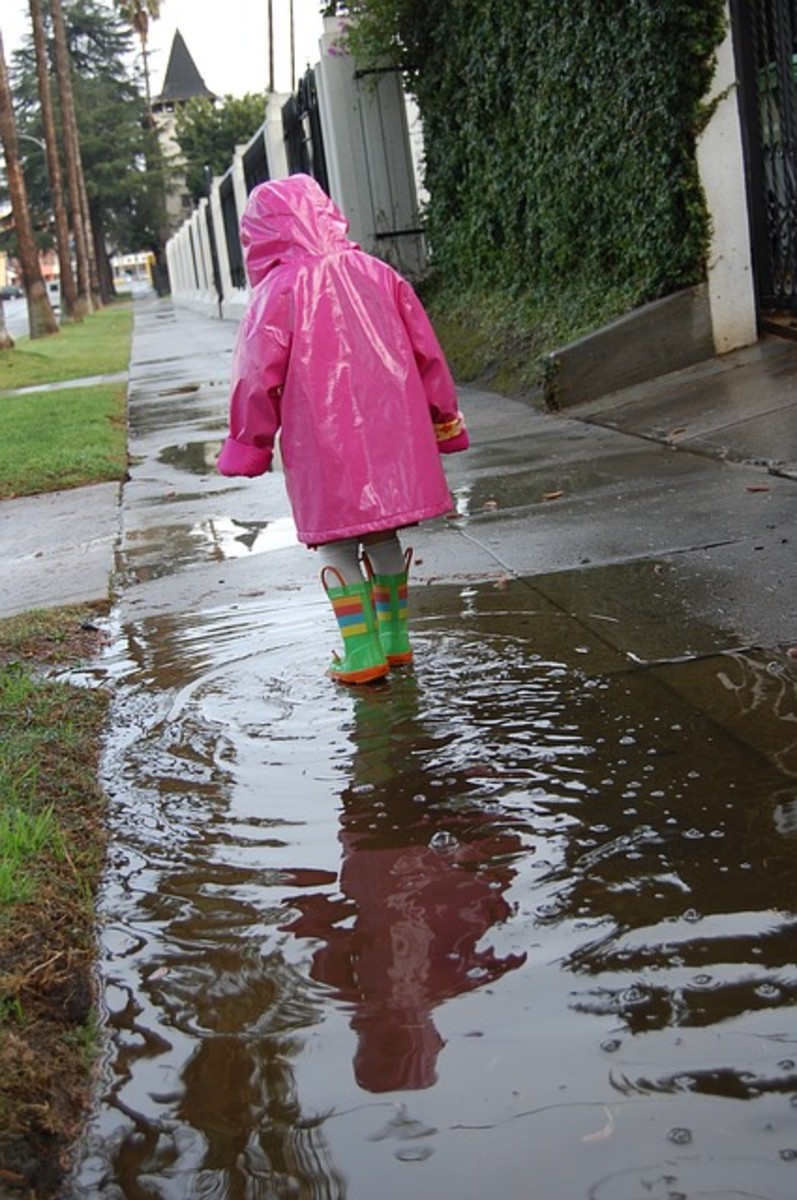 A child wears her matching pink and green rain gear on a very wet day.