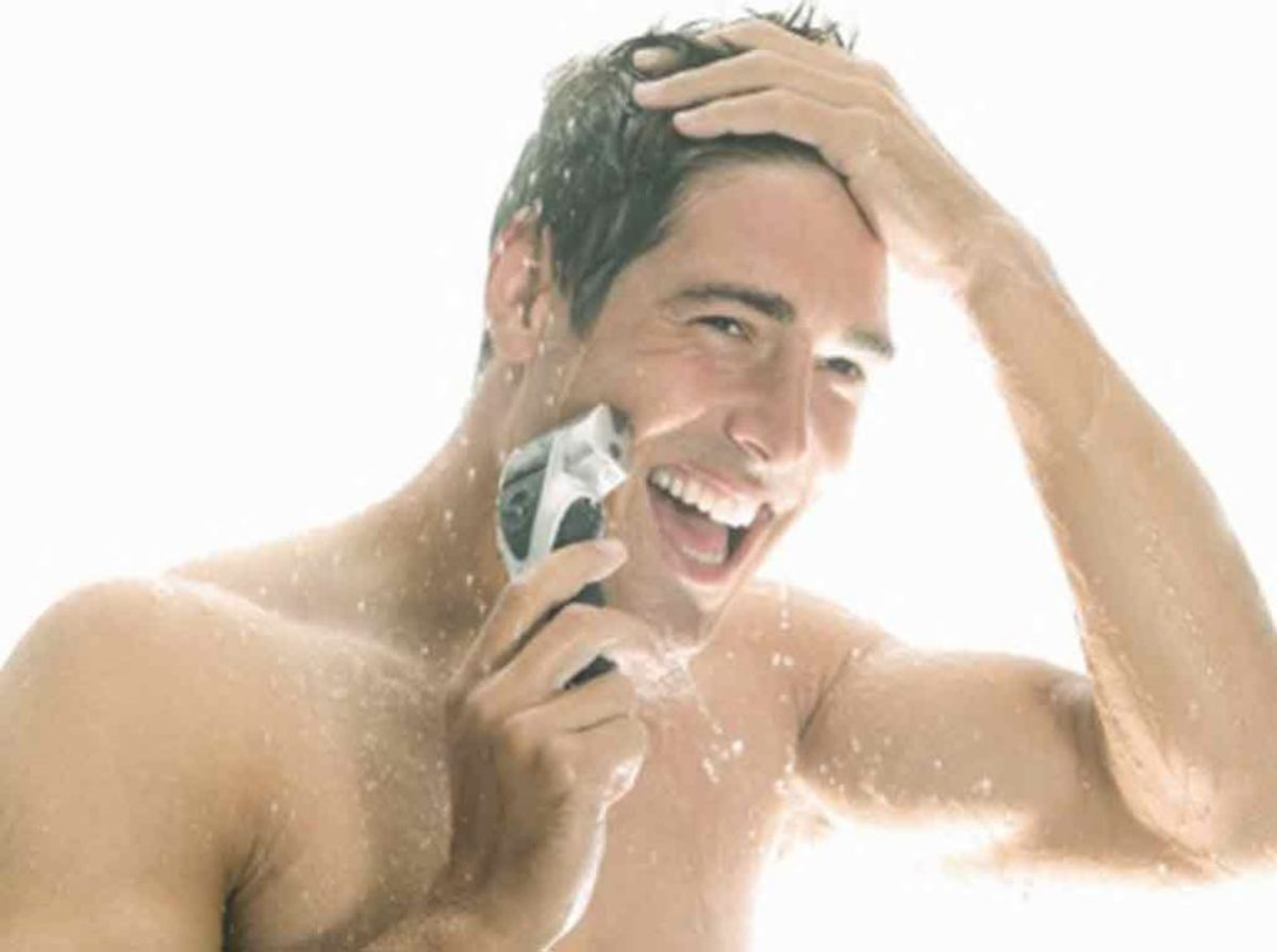 This is a happy man. It due to him shaving first, then showering or has he already showered and now shaving?