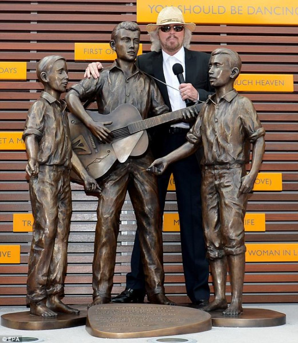 Posing alongside a bronze statue featuring the group barefoot between the ages of nine to twelve, Barry Gibb officially opened a commemorative walkway, known as Bee Gees Way, Redcliffe, Queensland
