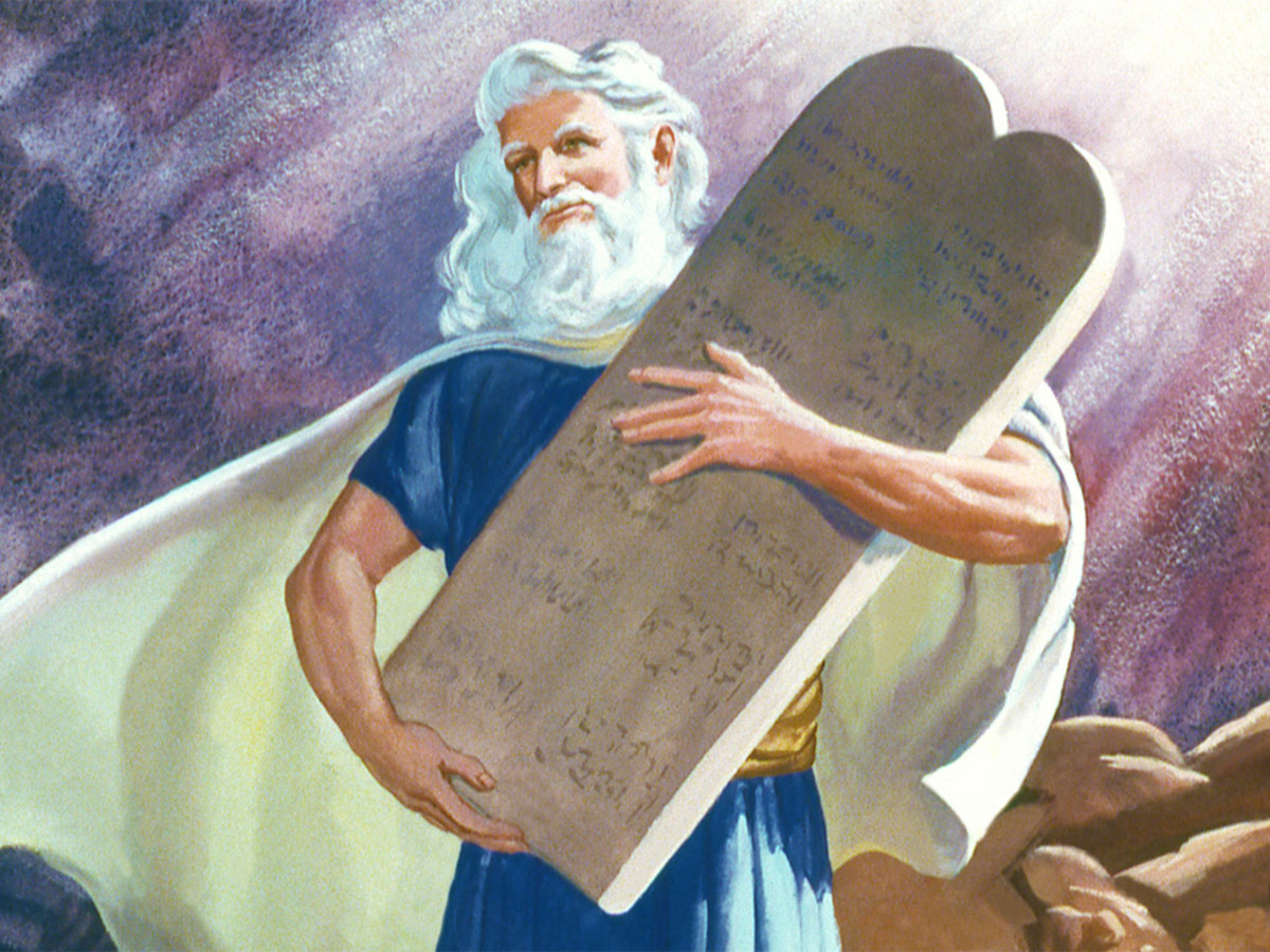 Moses with the Ten Commandments written on stone tablets by the hand of God.