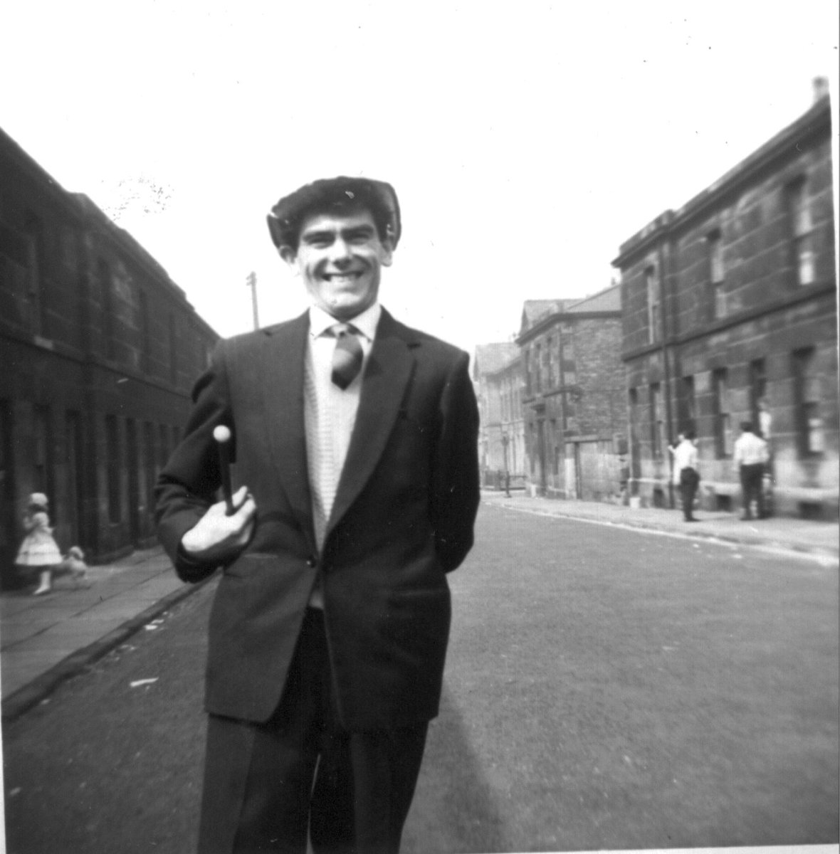 Tommy standing in the Street wearing a tophat the top of which cannot be seen properly