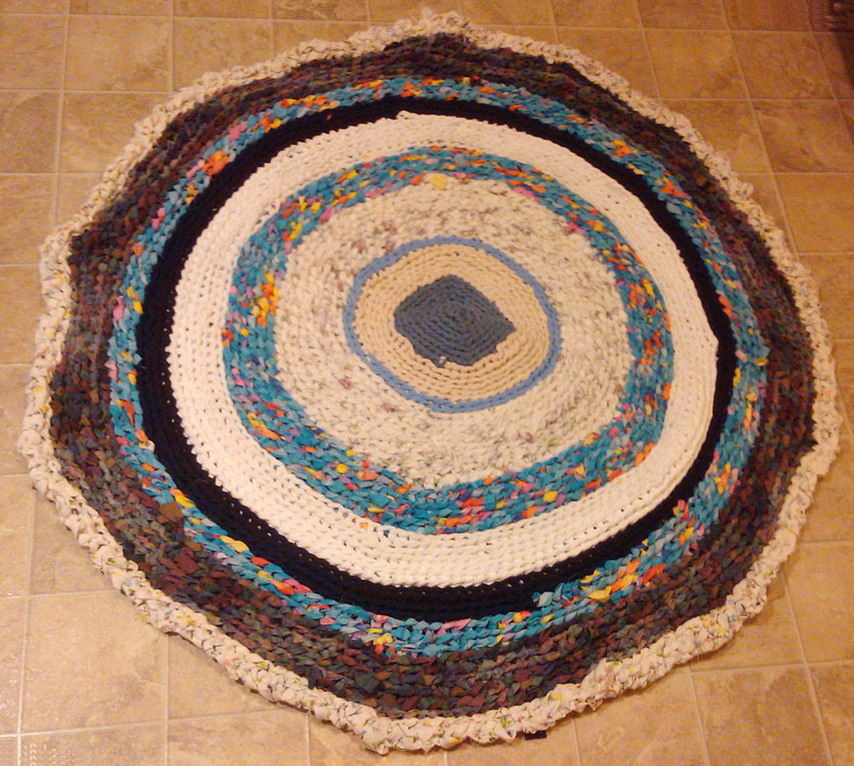Rug constructed out of fabric strips cut from second use t-shirts and bed linens.