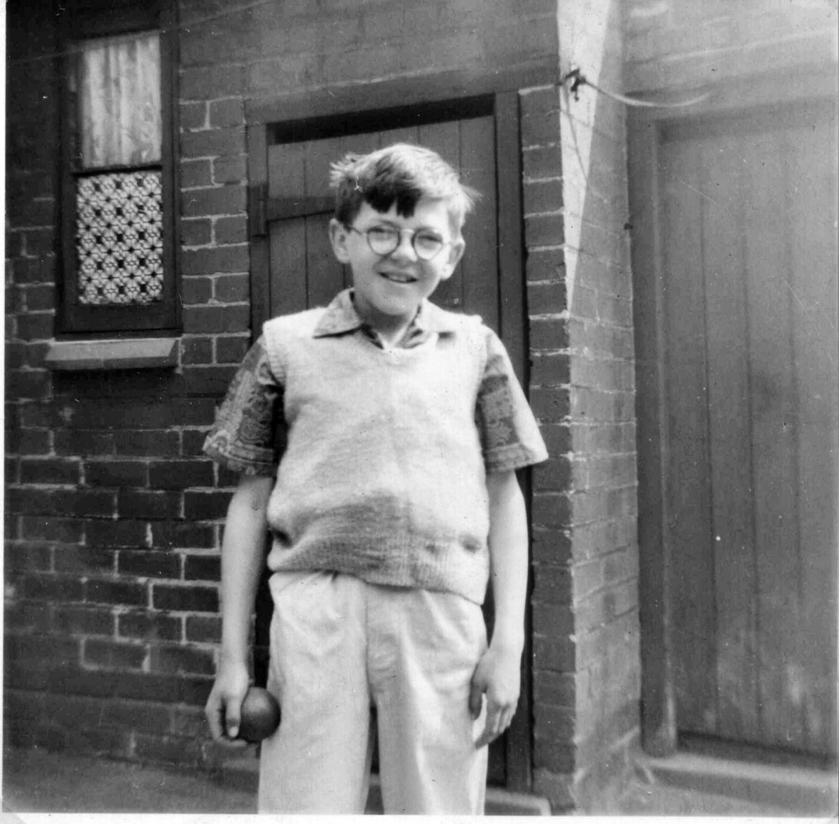 My brother much younger stood in front of our nextdoor neighbour's coal house and the outside toilet in our shared back yard.