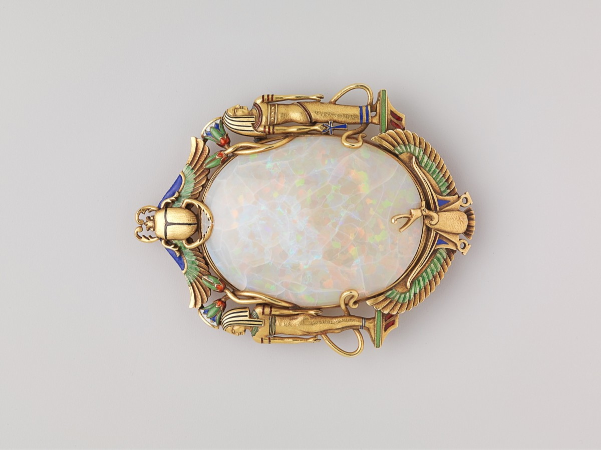 My reflection's brooch bore a scarab.
