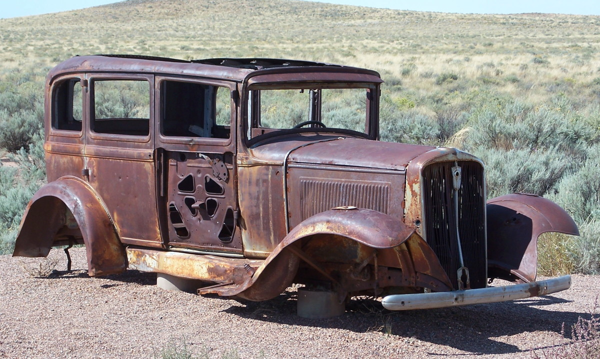 A rusty abandoned car is an antique desert sculpture.