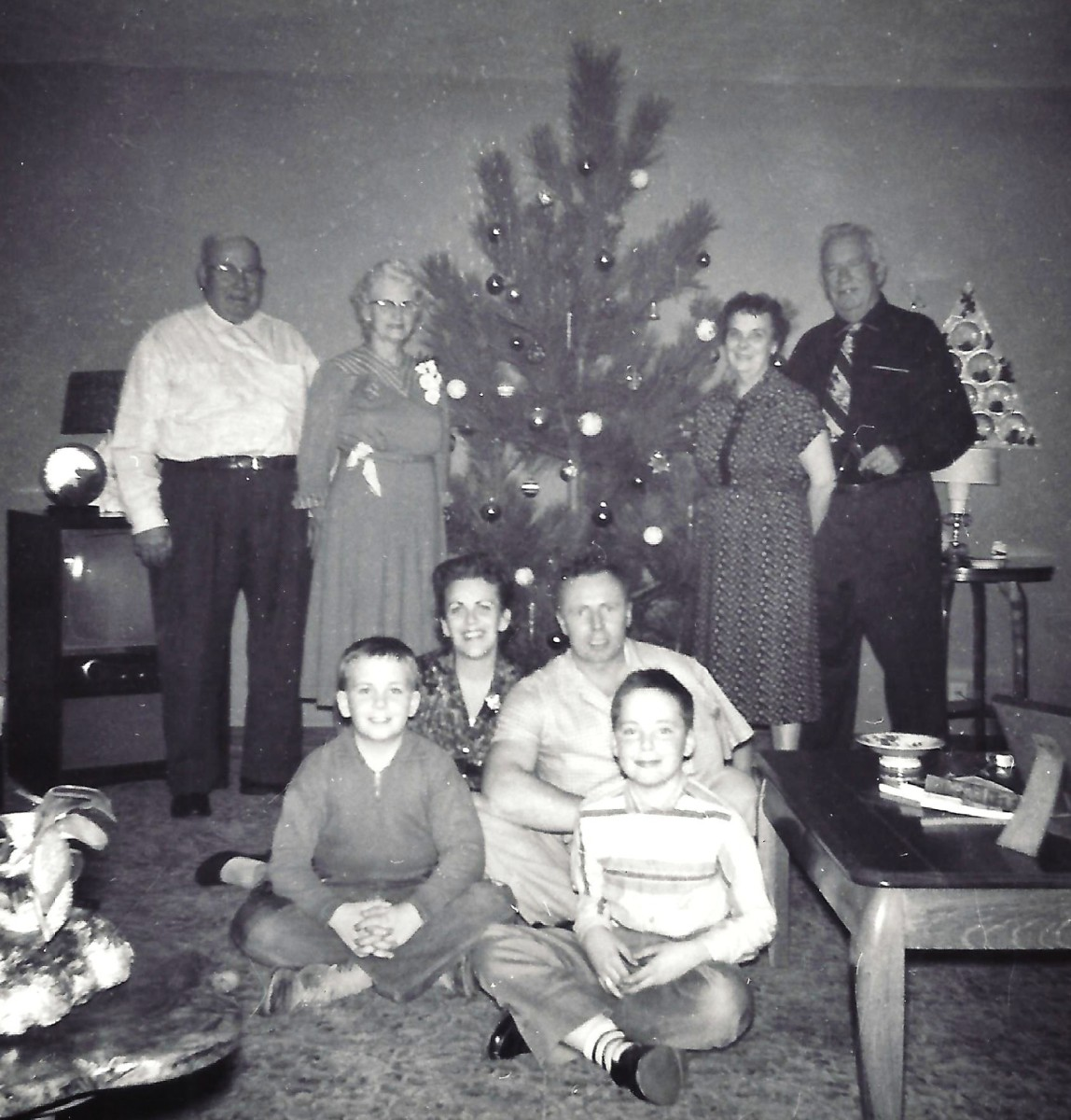 My parents and brothers seated with both sets of grandparents on either side of our Christmas tree.