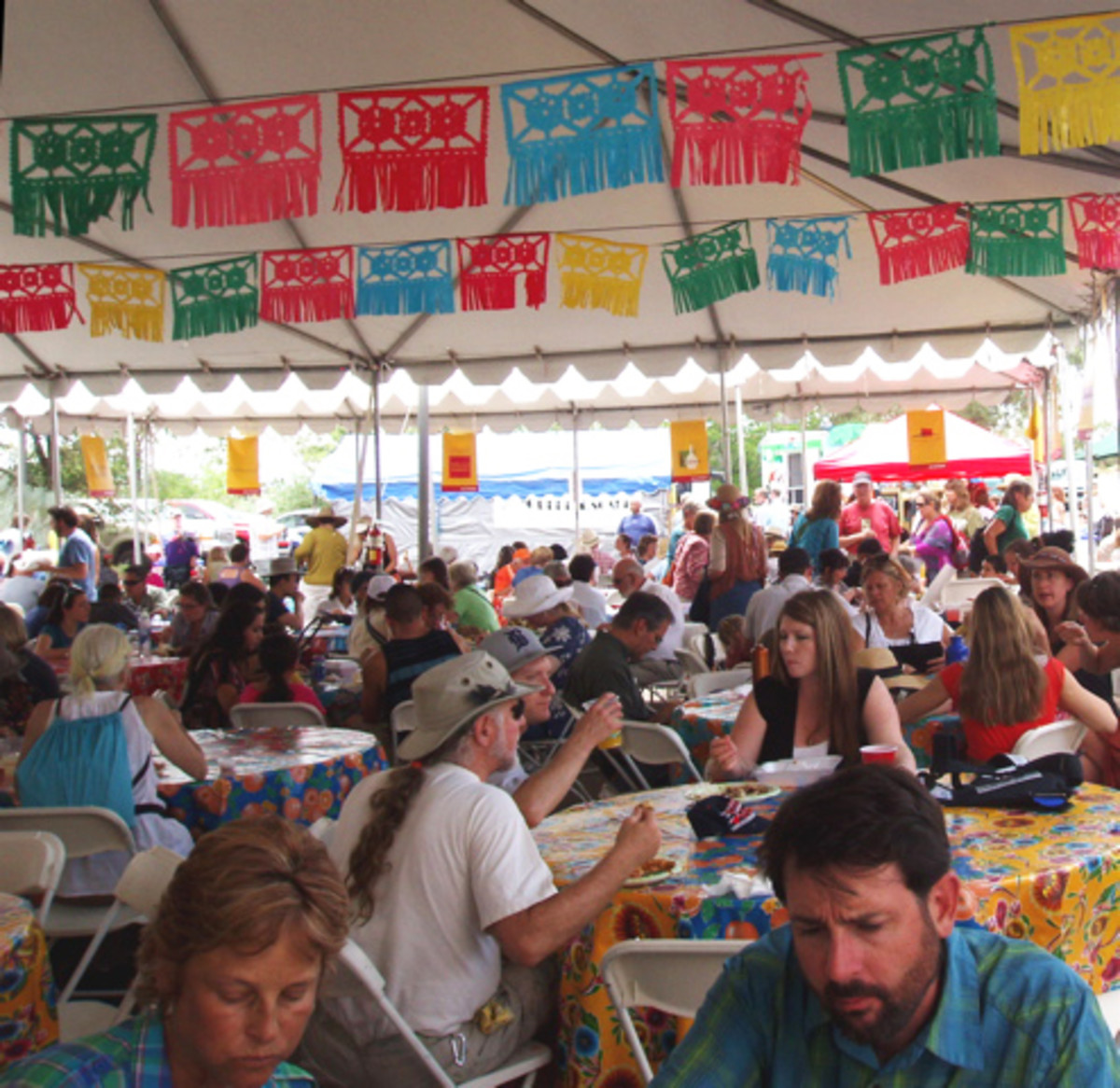 Attendees share an outdoor tent, while eating meals bought at ethnic food booths.