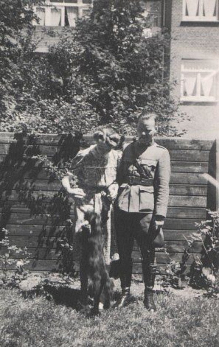My dad in army uniform with my mom in their garden with the dog Omar, a wedding present from my dad to my mom.