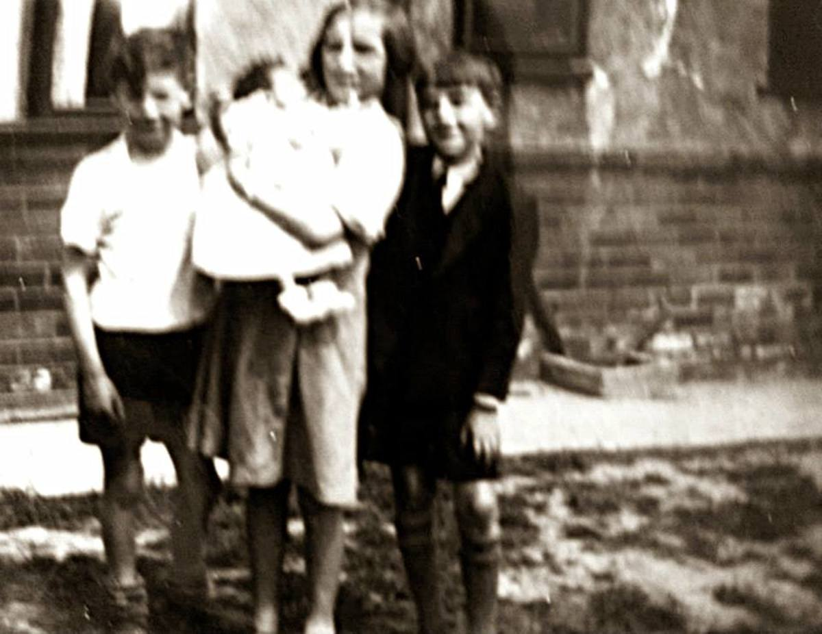 Mum as a child (holding her baby cousin, Shirley Brown) with her little brother Ken on the left and a neighbour's son on the right. They were playing in the street where they grew up in Leeds, Yorkshire.