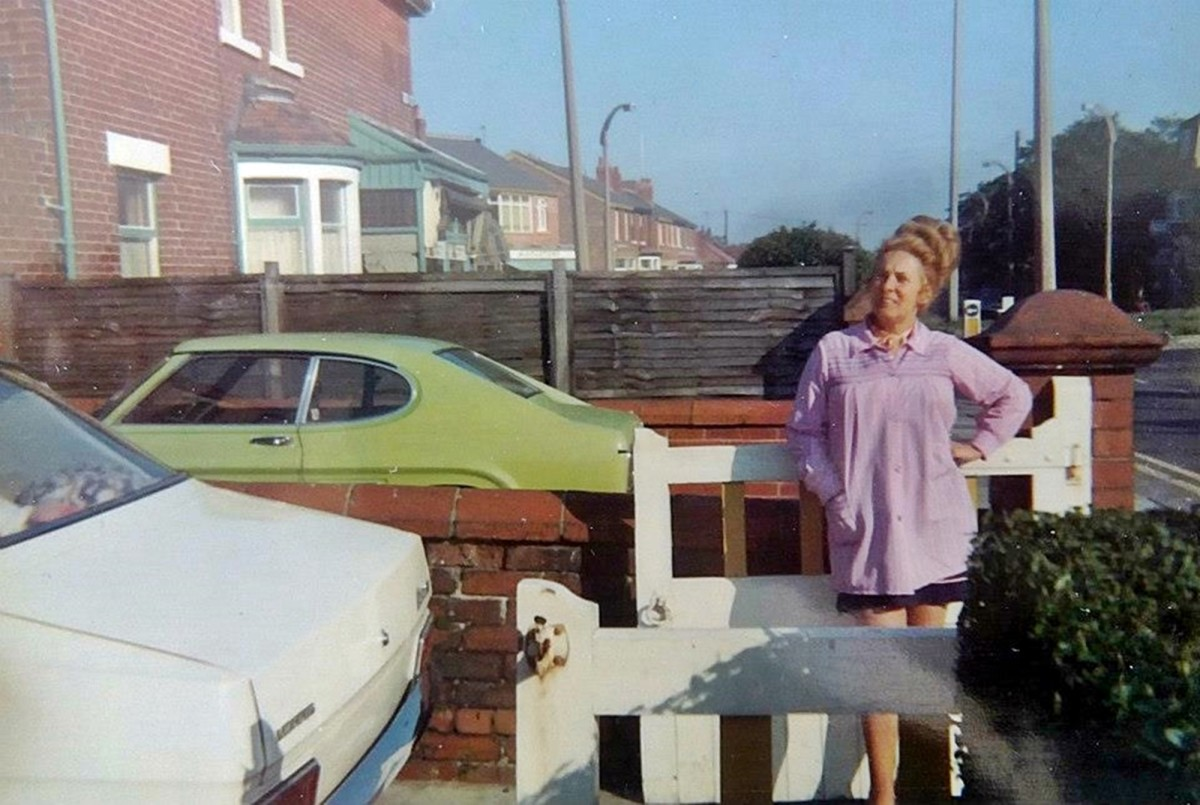 Mum in the'70s taking a breather after work. She is standing in our front garden enjoying the early evening sunshine.