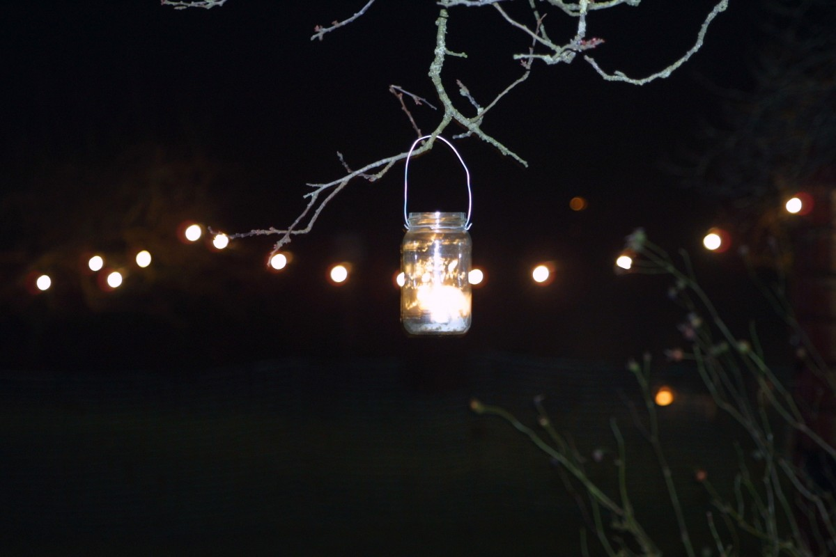 The orchard is lit up with torchlight, lanterns, and a bonfire.