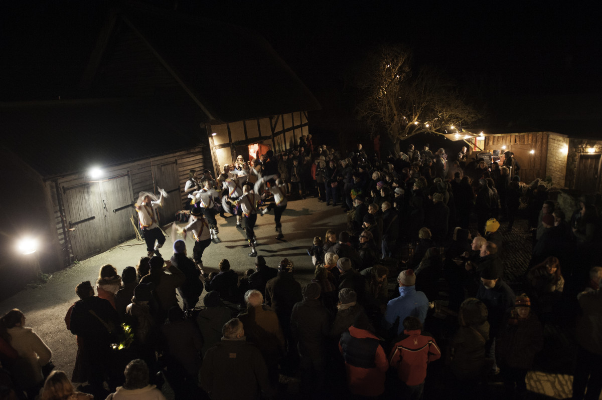 Crowds look on as the Morris Men make merry outside the barn.