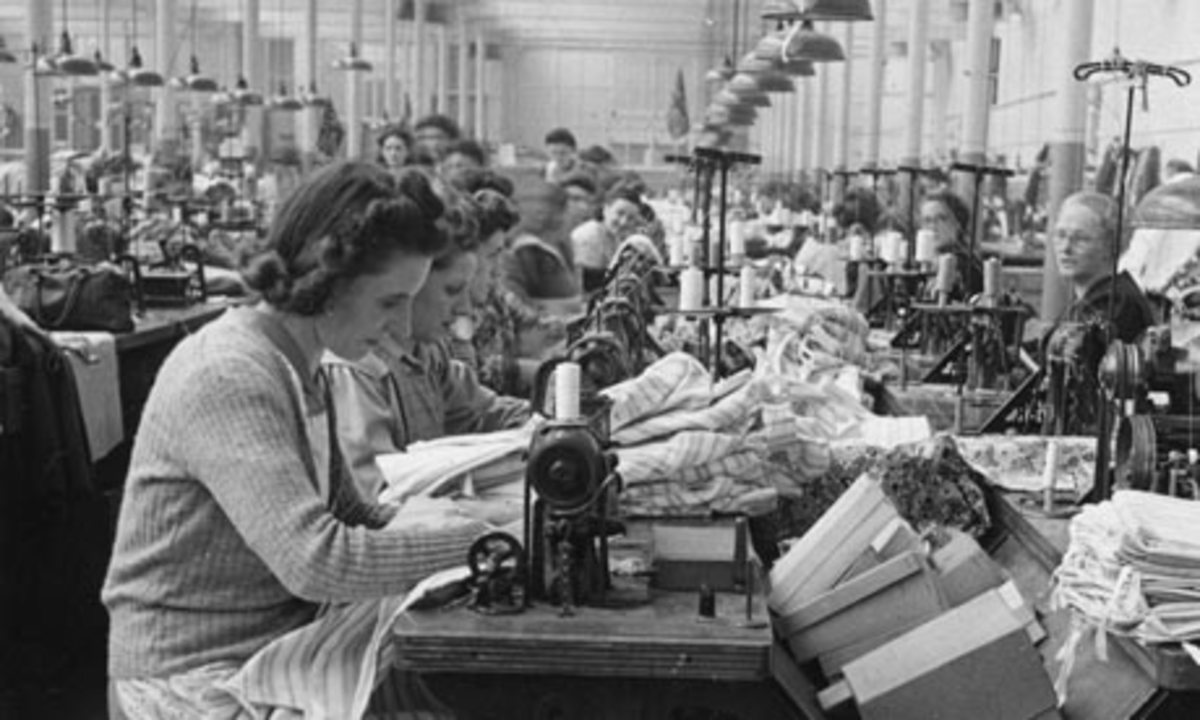 A woman sews shirts in a typical garment plant in the early 1960's.