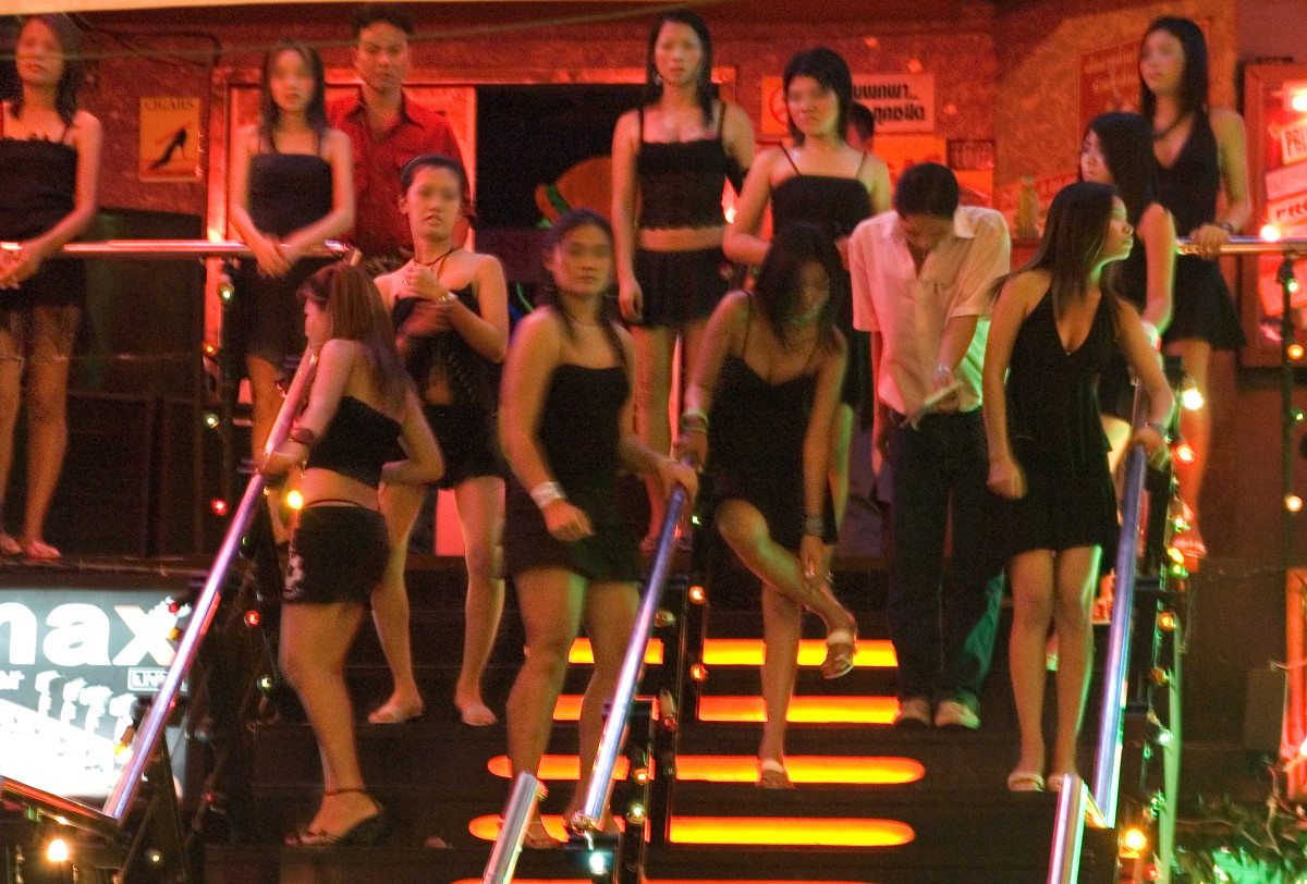 Prostitutes in front of a gogo bar in Pattaya, Thailand. Original text: Like slaves on an auction block waiting to be selected, victims of human trafficking have to perform as they are told or risk being beaten.