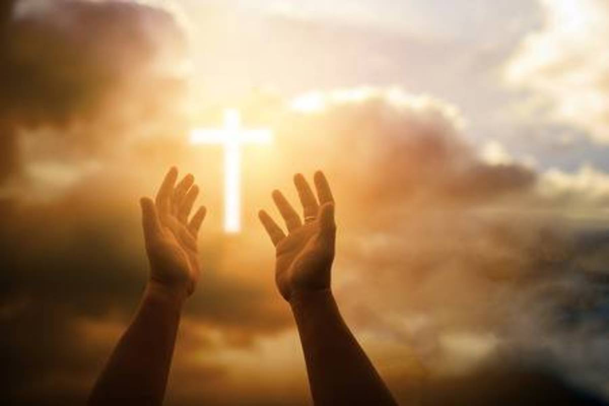 A pair of hands reaching up to the cross
