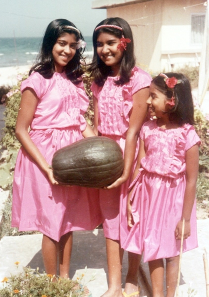 Pic3: My Younger Sister and I Holding the First Dark Green Pumpkin from Our Garden While My Little Sister Looks On