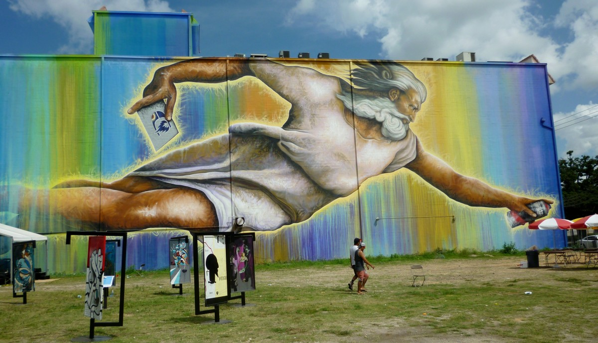 Preservons la Creation with Open The Door art in front of the giant mural