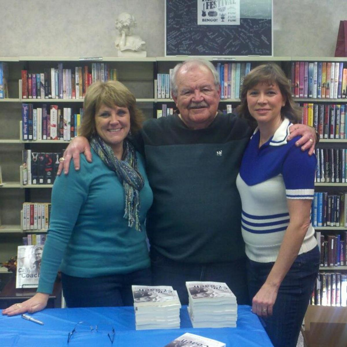 My dad and I at a book signing in 2012. My friend Annette showed up in her cheerleading sweater to surprise my dad.