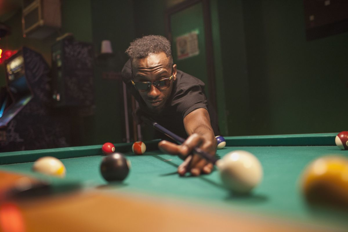"""Professional African-American billiards player """"Jeremiah Karne"""" lining up his classic """"Akachi God's hand Billiards Shot"""" in the Mens Man-Cave Cue Sports Semifinals"""