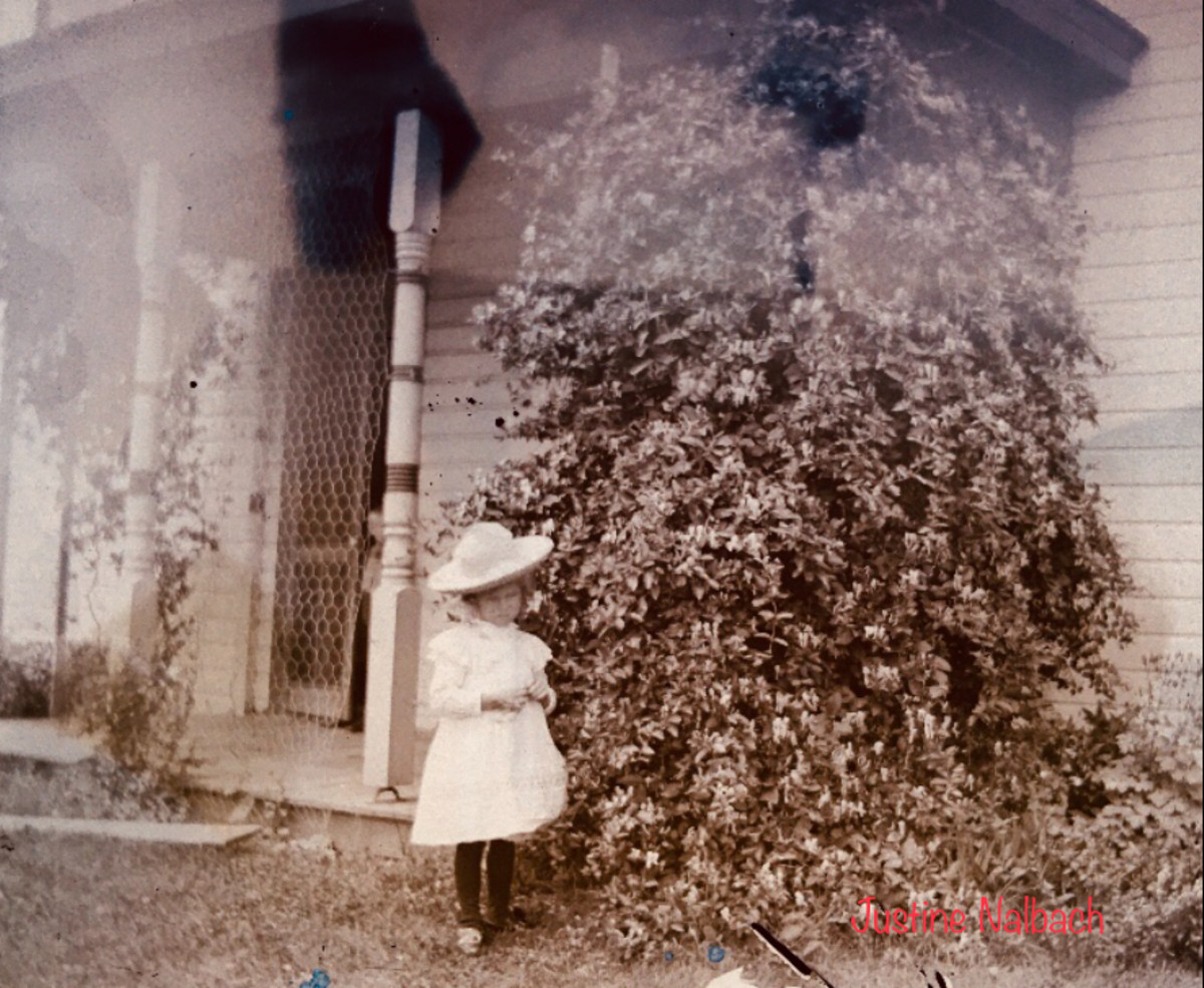 Little girl stands in front of the porch at Vollmars Farm