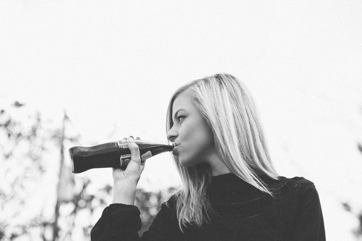 Notice: this pretty girl is enjoying A Soft Drink in a bottle that the brand is NOT noticeable.
