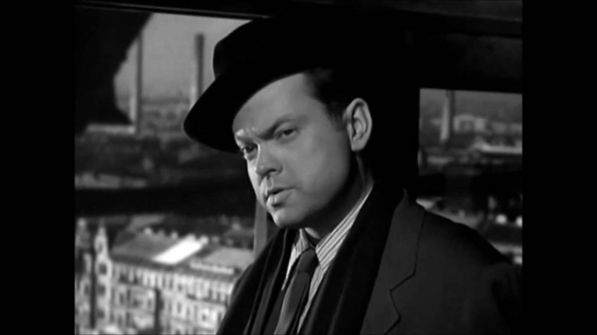 """""""He-e-ere's Harry!"""" Orson Welles discusses the finer points of his business with friend Joseph, """"Butt out!"""" is the essence of his message."""