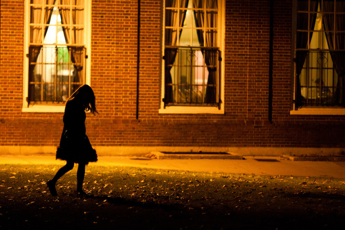 Flickr for use.  Woman walking in street at night