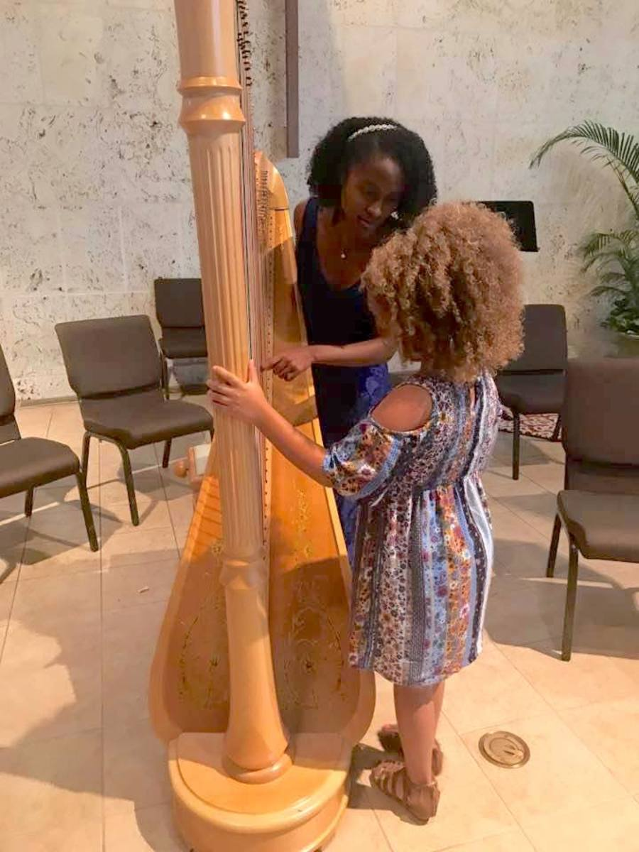 Angelica showing Sophie Green how to play a glissando on the harp.