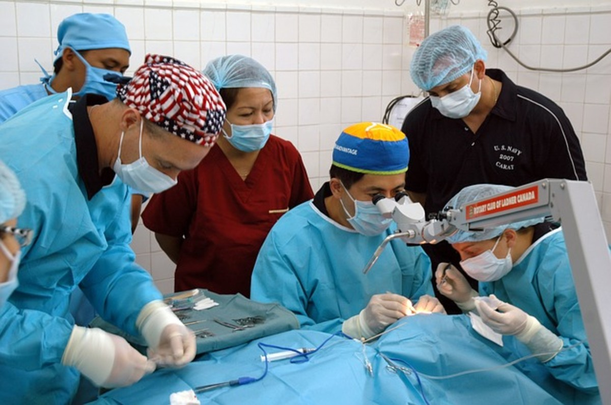 Circulating nurse is actively watching the surgery and sterile field.