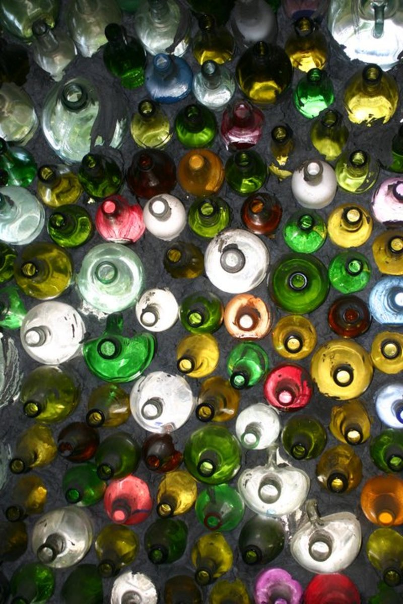 An artist mortars glass bottles to form an unusual building wall