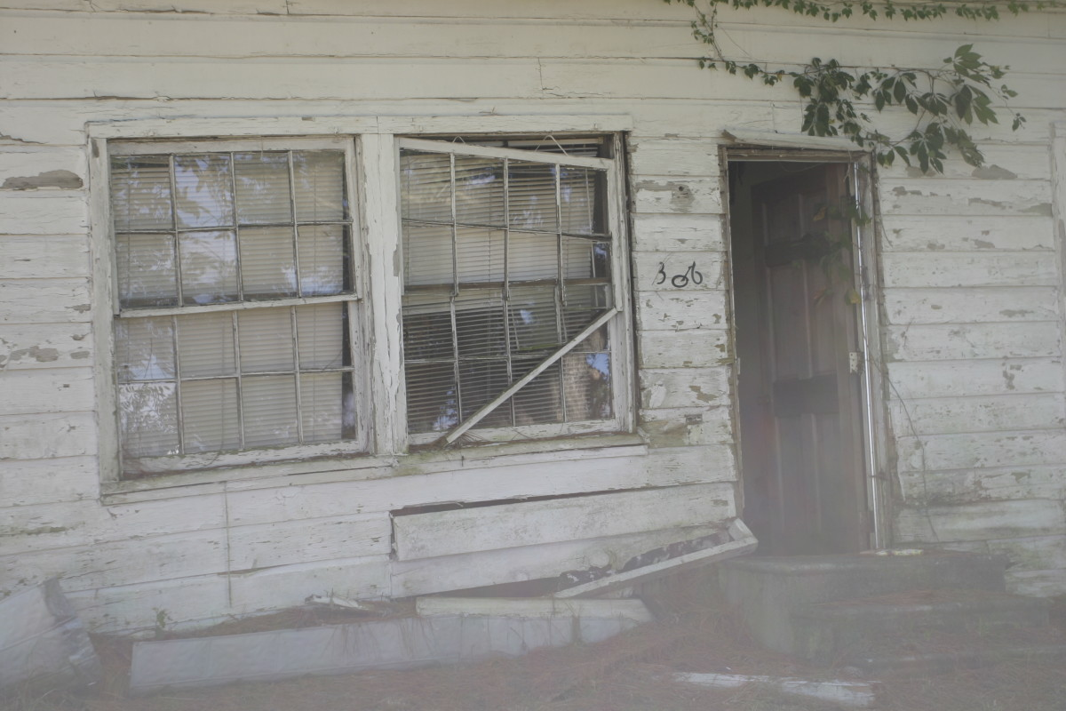 Mist flows from the doorway of an abandoned house, while something appears to peek from behind the window.