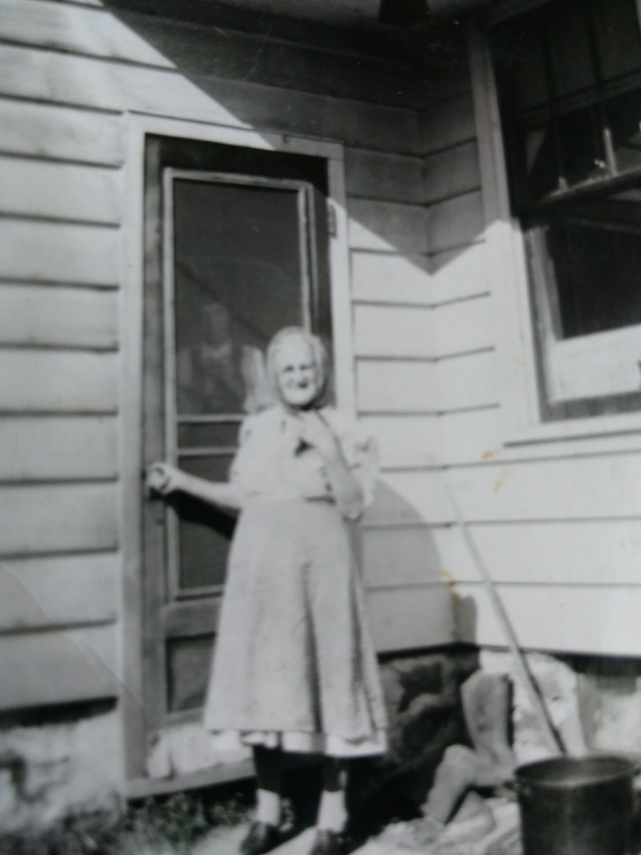 My little grandma outside of her home in probably the early 50s.  The man behind the screen door is probably great-uncle John.
