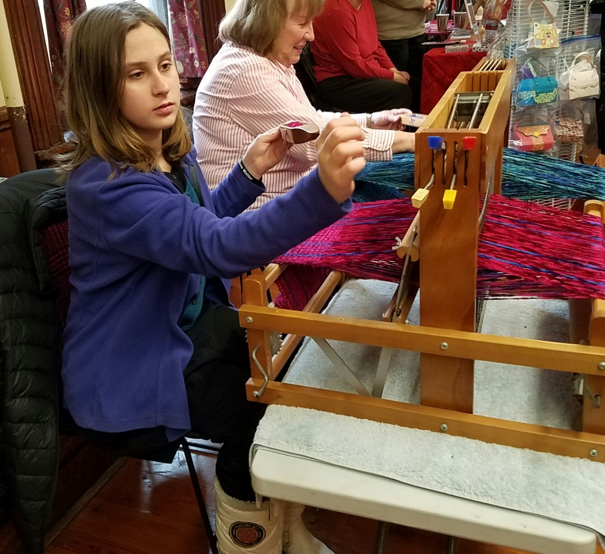 Learning to weave a winter scarf for herself at a recent local craft fair