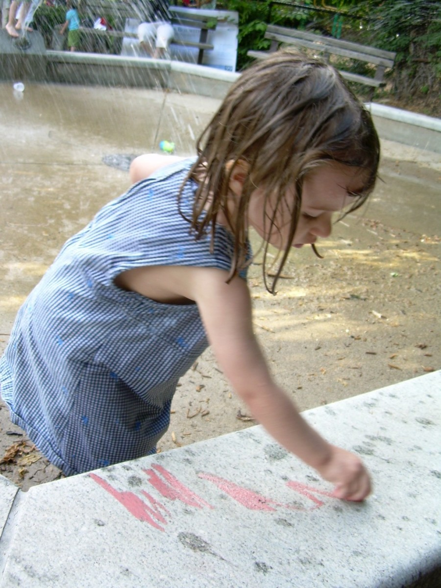 My young daughter drawing  in chalk on the wall of a water fountain at our local park
