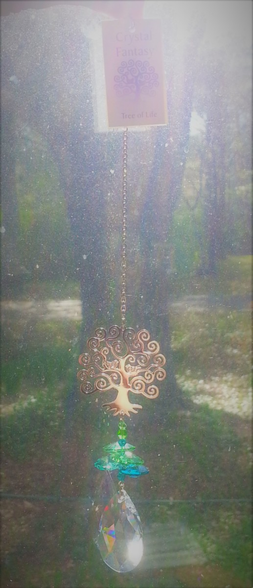 "The ""Crystal Fantasy Tree of Life"" hanging crystal from Pike's Nursery aligned with an actual tree in our front yard. It shows the symbolism of the trunk, the roots in the ground, water table feeding the roots, and luminous glow I felt that day"