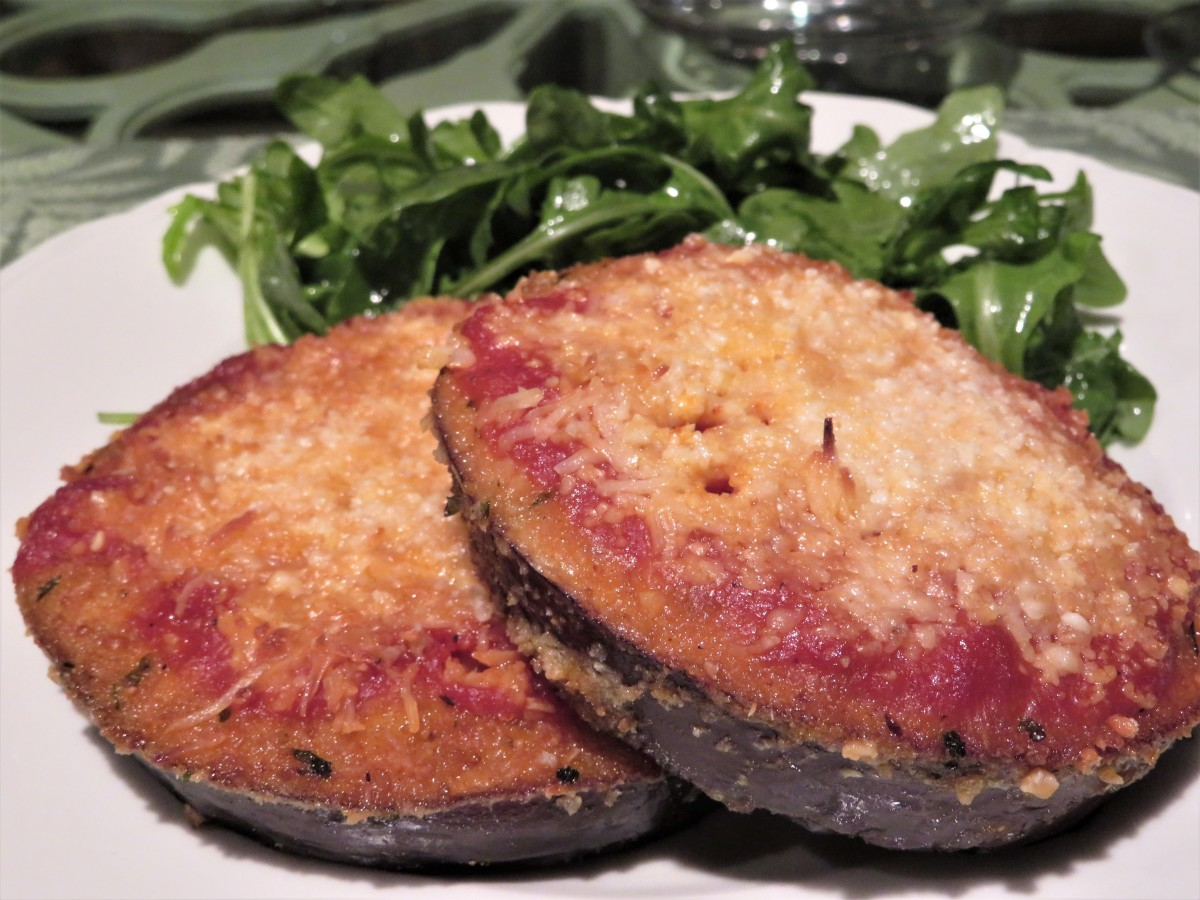 Eggplant Parmesan on a plate with arugula salad