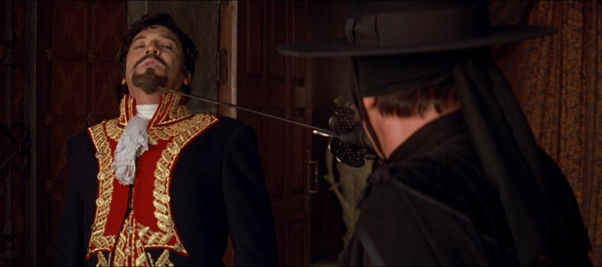 Zorro (Hopkins) threatens Don Rafael Montero.